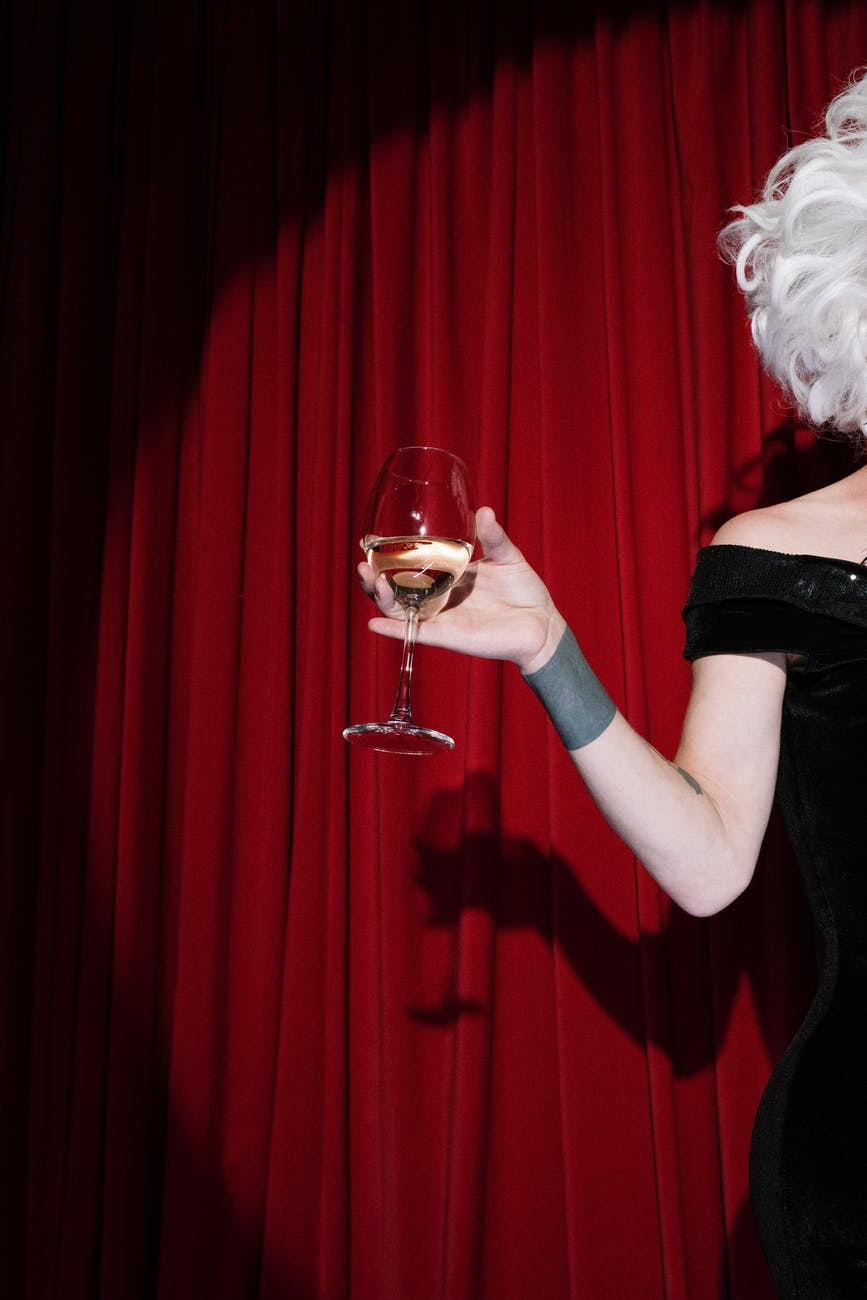 person on stage holding a glass of wine