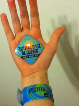 Le bracelet à puce du festival, et le macaron, qui ne sert à rien sinon à te faire clignoter le téton avec une LED rouge.