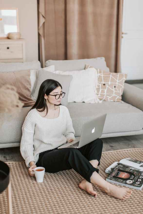 young woman using laptop on floor near sofa