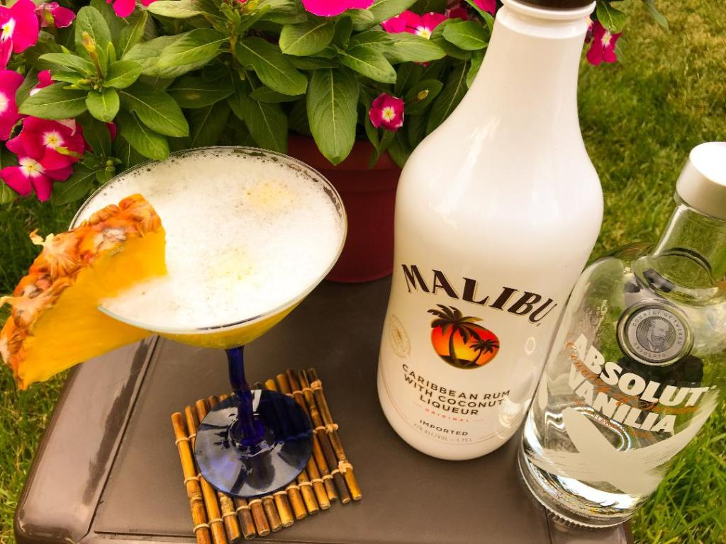 Pina Colada Martini made with Absolut Vanilla Vodka, Malibu Coconut Rum, Pineapple Juice, Simple Syrup, and fresh pineapple for garnish.