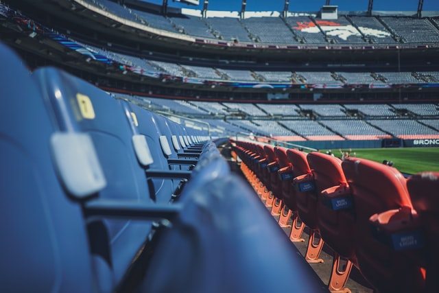 Empty stadium seats with the Broncos logo in the background at Empower Field at Mile High in Denver, Colorado.