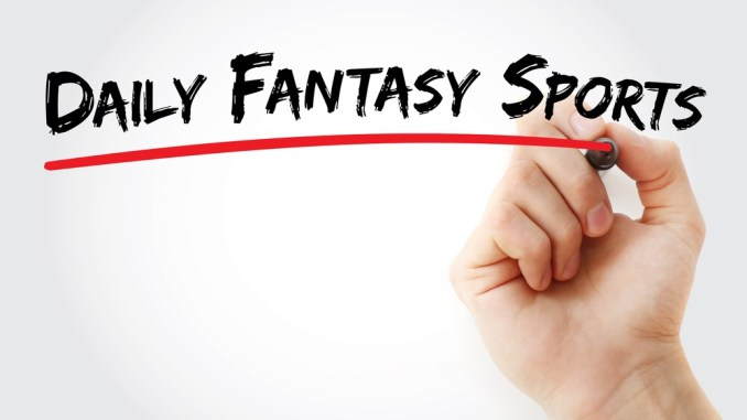 "A person writing on a white board the words ""Daily Fantasy Sports"" in a black marker and then underlining them with a red marker."