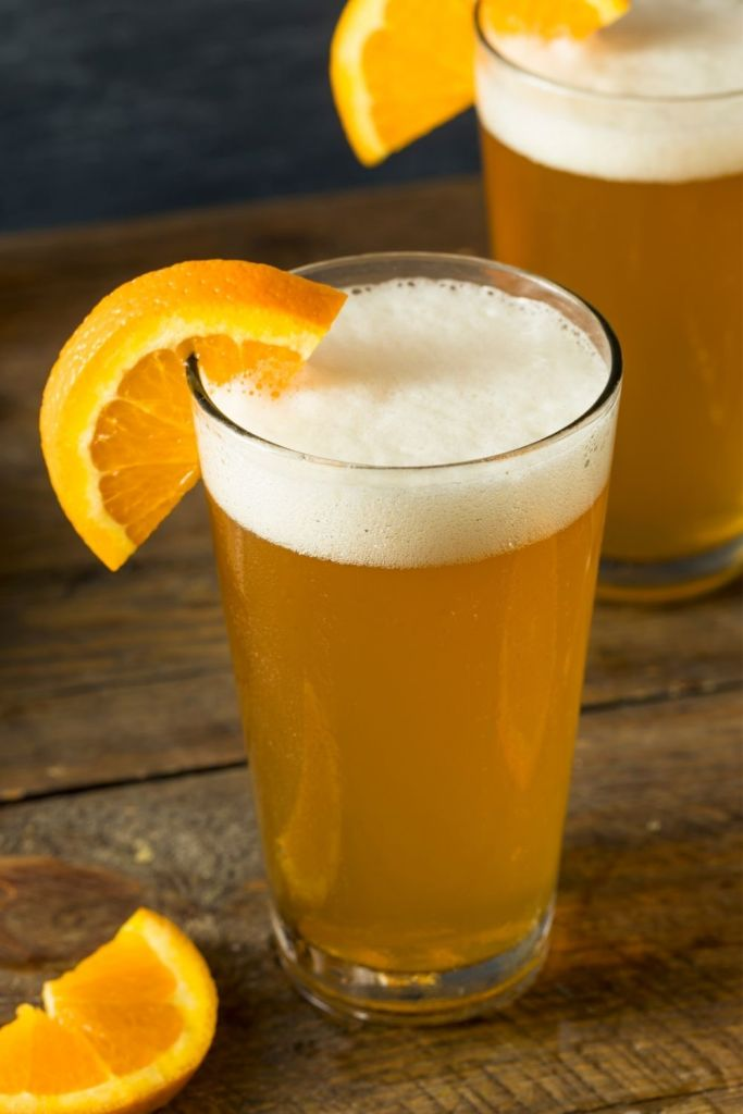 A couple of pints of Beermosa's garnished with fresh orange slices sitting on a wooden table.