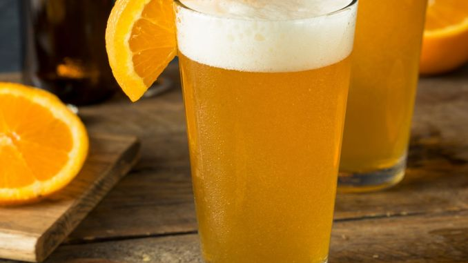 A couple of Beermosa's garnished with fresh orange slices sitting on a wooden table