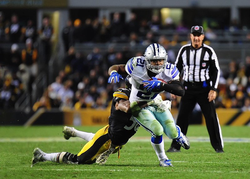 NFL Dallas Cowboys Ezekiel Elliott running with the football while a Pittsburgh Steeler defender tries to tackle him