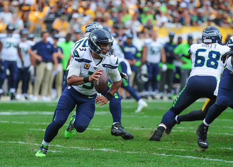 NFL Seattle Seahawks quarterback Russell Wilson rolling out of the pocket for a pass in a football game