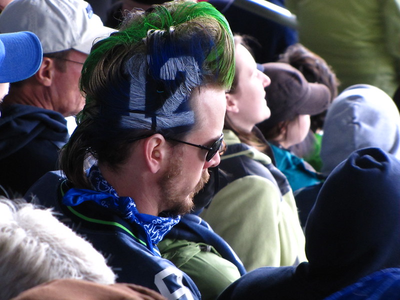 A Seattle Seahawks 12th man fan with a neon green and blue mohawk and the number 12 in bright white on the side of his head