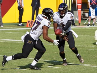 NFL Baltimore Ravens running back J.K. Dobbins taking a handoff from quarterback RG3