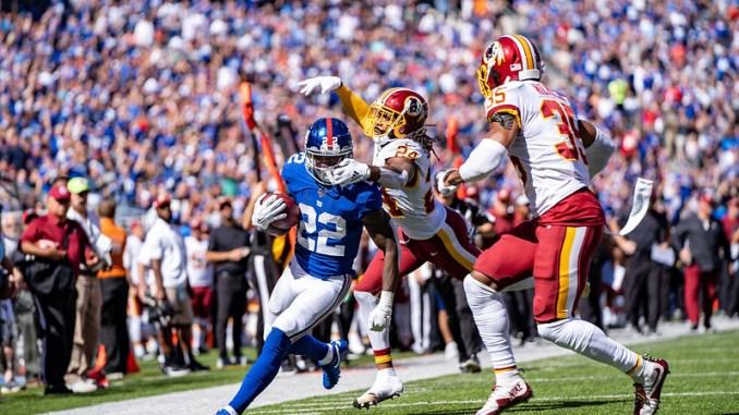 New York Giants running back Wayne Gallman avoiding a tackle from a Washington Football Team defender.