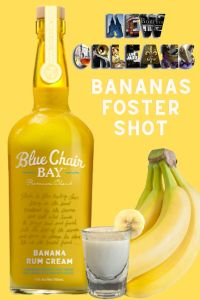 A Bananas Foster Shot on a yellow background with a New Orleans city themed text. Sitting next to a bottle of Blue Chair Bay Banana Rum Cream and a bunch of bananas.