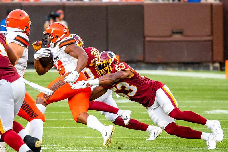 Cleveland Browns running back Nick Chubb avoiding a tackle against the Washington Football Team defender.