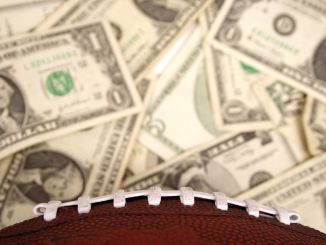 A football sitting on top of a pile of $1 and $5 bills