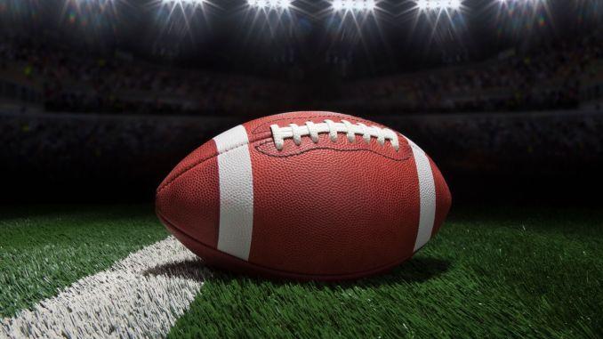 Football on a field under stadium lights.