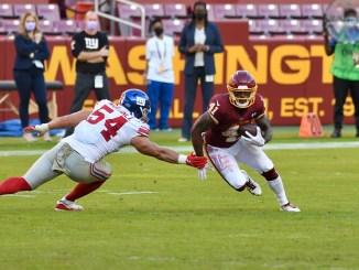 Washington Football Team running back J.D. McKissic avoiding a tackle against a New York Giants defender.