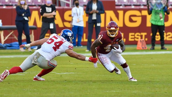 Washington Football Team running back J.D. McKissic avoiding a tackle against a New York Giants defender.