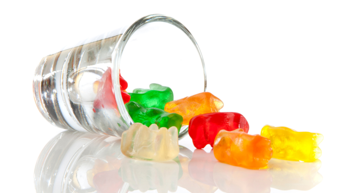 A clear shot glass tipped over with green, red, orange, yellow, and white gummy bears spilling out.