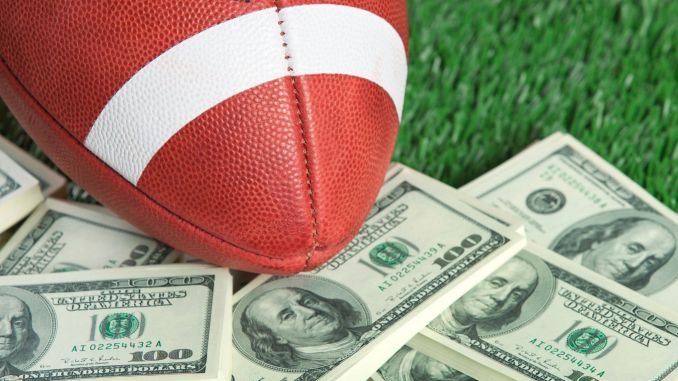 A football laying on a pile of stacks of $100 bills.