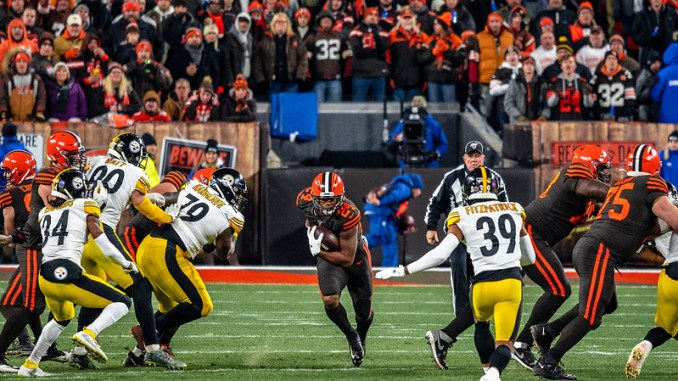 NFL Cleveland Browns running back Nick Chubb running between a big hole in the Pittsburgh Steelers defense.