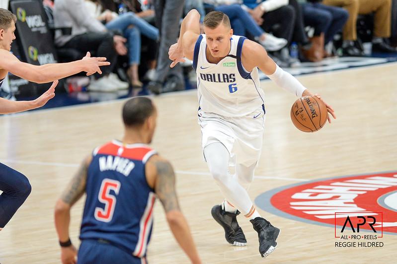 NBA Dallas Mavericks center Kristaps Porzingis driving to the basket against a Washington Wizards defender.