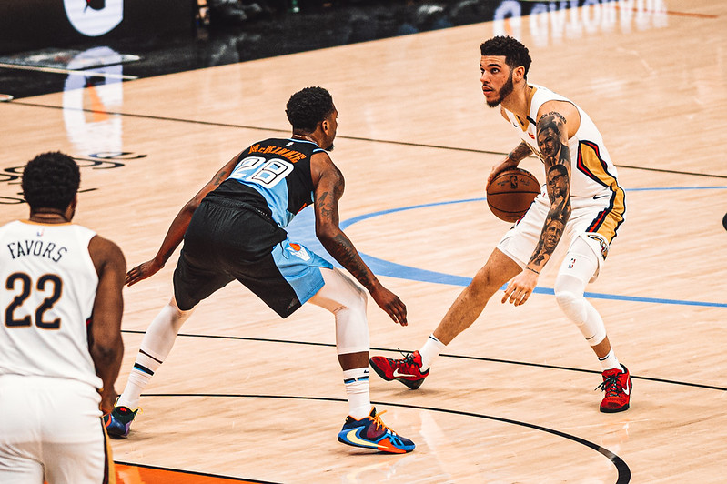 NBA New Orleans Pelicans point guard Lonzo Ball dribbling the basketball against a Cleveland Cavaliers defender.