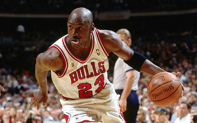 NBA legendary Chicago Bulls shooting guard Michael Jordan dribbling the basketball with his tongue sticking out.