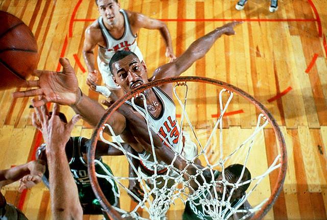 Legendary NBA center Wilt Chamberlain battling at the rim against defenders.