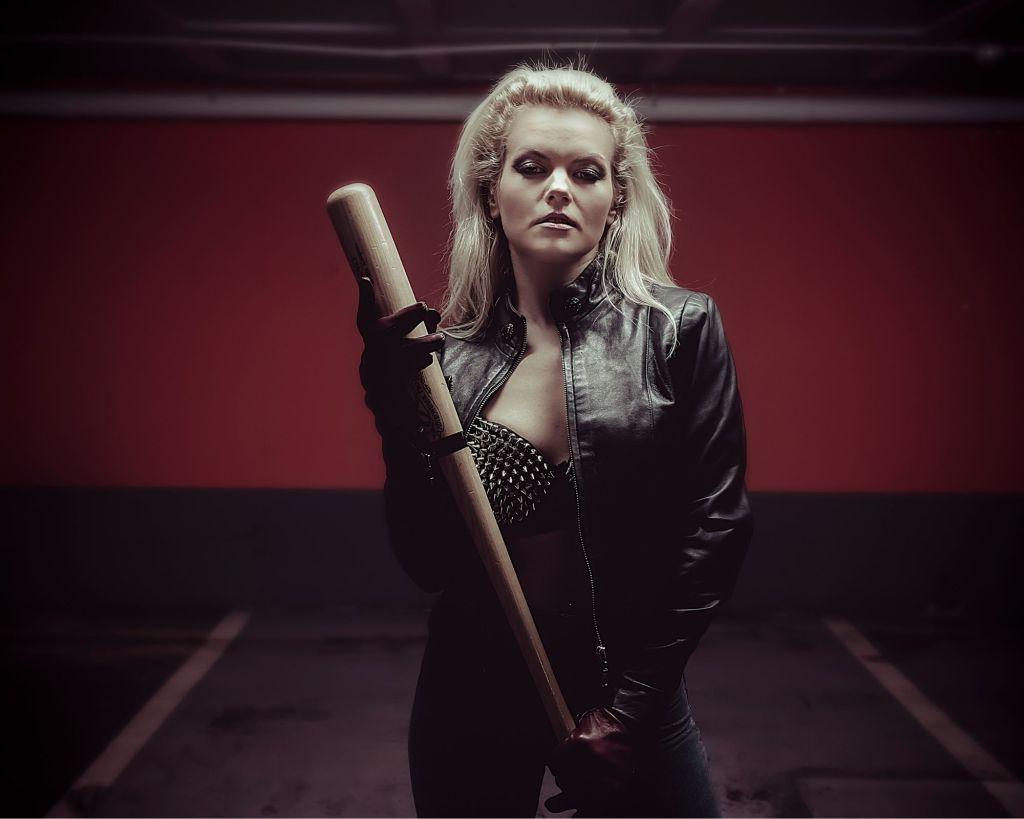Blonde woman holding a baseball bat.