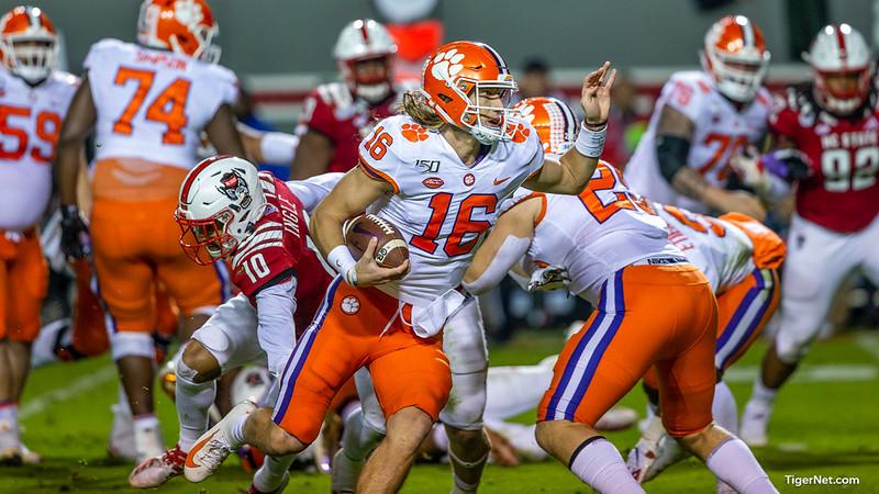 Former Clemson University quarterback Trevor Lawrence running with the football against North Carolina State defenders.