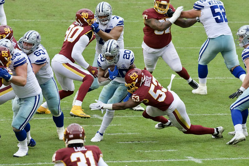 Dallas Cowboys running back Tony Pollard breaking a Washington Football Team defender tackle in a NFL football game.