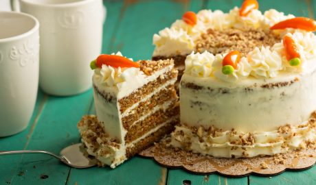 Slice of carrot cake with cream cheese frosting on wooden table