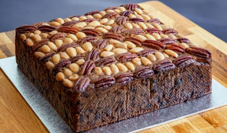 Square fruit cake decorated with almonds and pecans