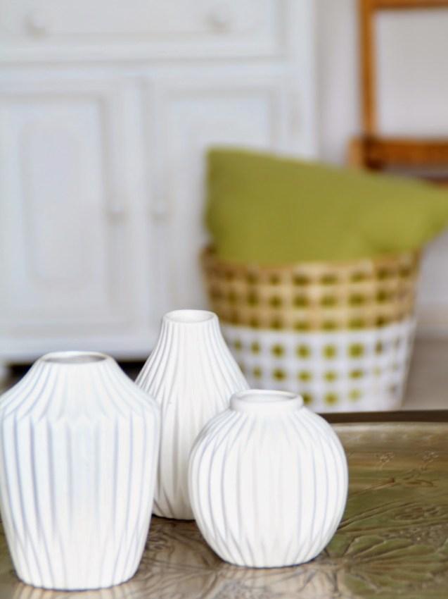drei weiße Vasen im Vordergrund verschwommen im Hintergrund Korb mit grünem Kissen und alter Kinderstuhl