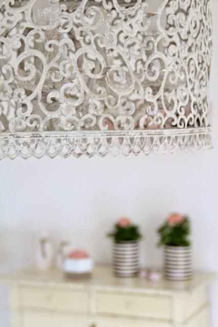Verschnörkelte weiße Lampe im Vordergrund mit verschwommener Dekoration im Hintergrund