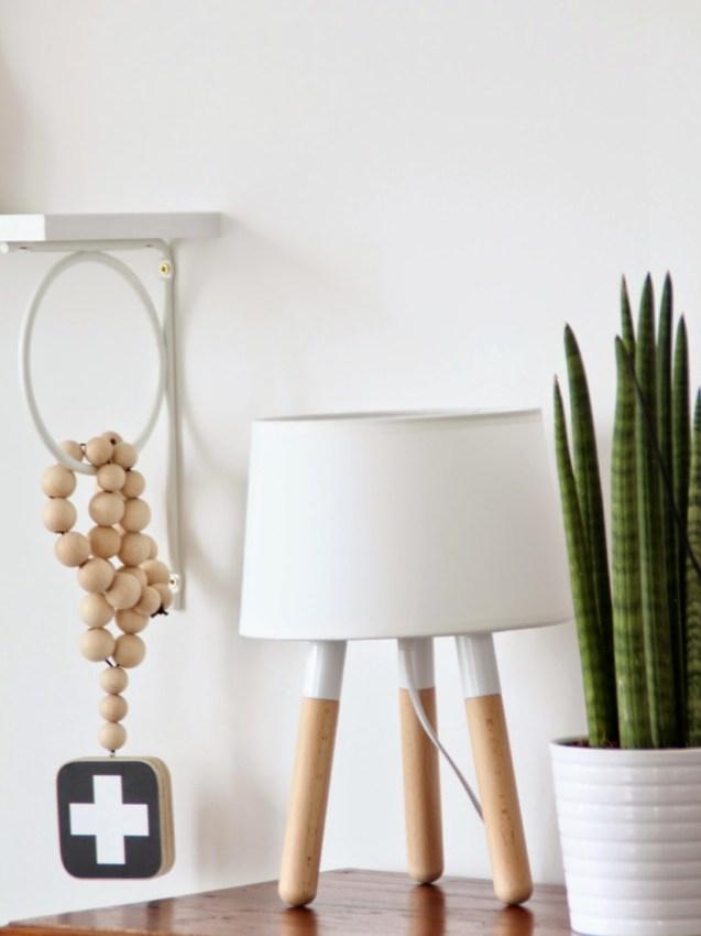 Weiße Lampe mit weißem Übertopf und Planze auf Kommode daneben hängt eine Kette aus Holzkugeln mit weißem Kreuz auf schwarzem Grund