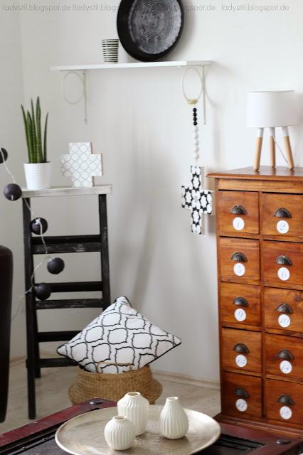 Ecke des Wohnzimmers mit schwarzer Leiter Kommode Regal und vielen Dekoartikeln wie Kreuzkette, Vasen und Kissen in schwarz weiß