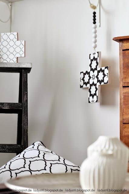 Vergrößerte Ansicht der Wohnzimmerecke mit Kreuzkette und Leiter im Hintergrund im Vordergrund weiße Vasen auf Couchtisch