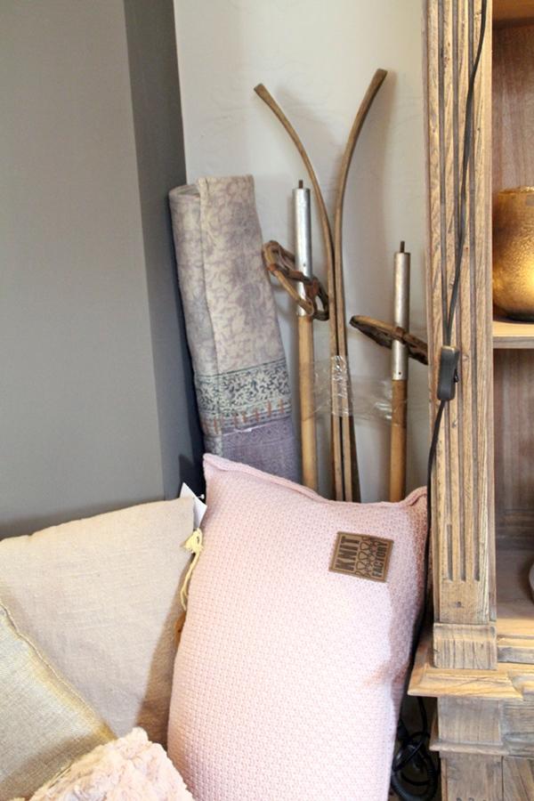 Blick in eine Ecke mit alten Holzskiern und einem gemusterten lila-beigem Teppich