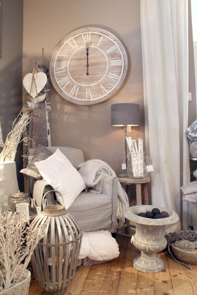 Sitzecke mit beigem Sessel und Wohndeko drumherum in beige grau mit großer Laterne aus Bast und Amphore sowie großer Wanduhr