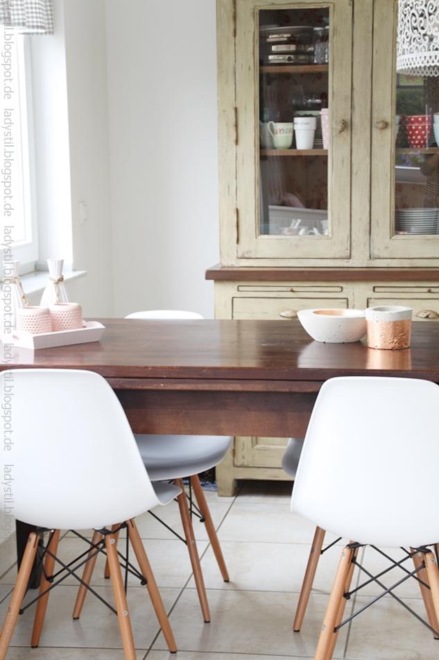 Esstisch dunkelbrau mit Eames Stühlen in weiß und Vitrinenschrank im Hintergrund