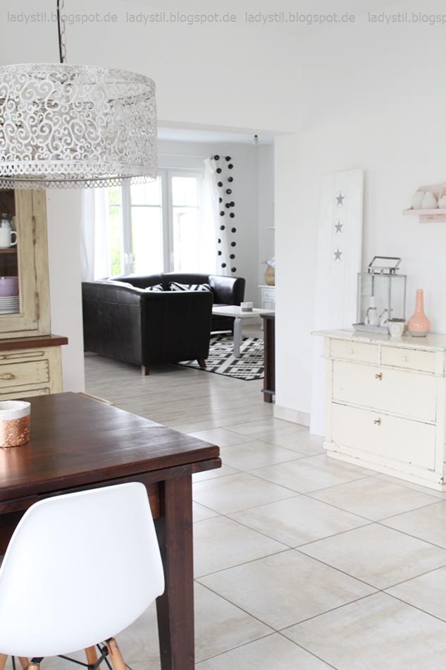 Blick vom Esszimmer mit dunkelbraunem Tisch und antiker beigen Kommode ins Wohnzimmer mit braunem Sofa und schwarzweißem Teppich von Ikea