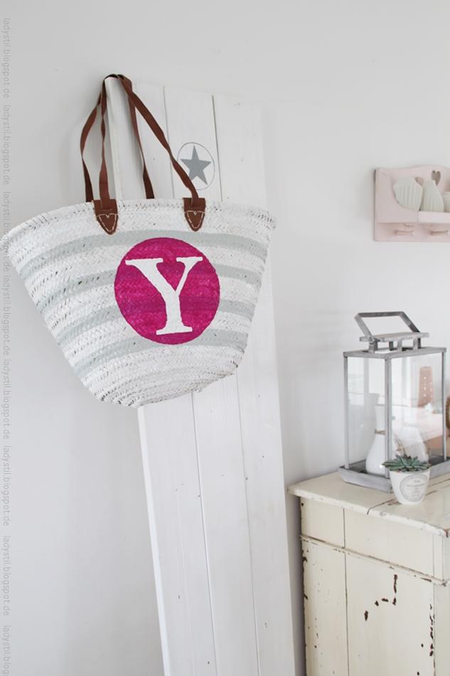 Weiß hellgrau gestreifte Korbtasche mit großem pinkfarbenem Kreis darin ein weißes Y hängt an einer Sternentafel rechts davon Kommode mit diversen Wohnaccessoires für den Bloggeroptimierungsfotowettbewerbbeipixum