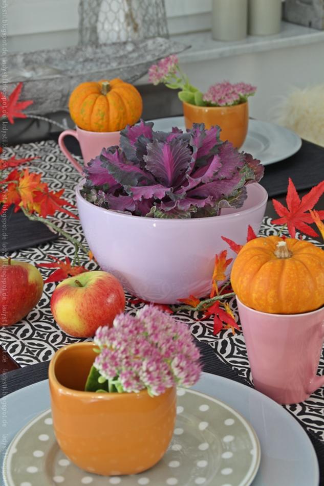 Herbstliche Tischdekoration in orange und purpur mit Kürbissen in orange