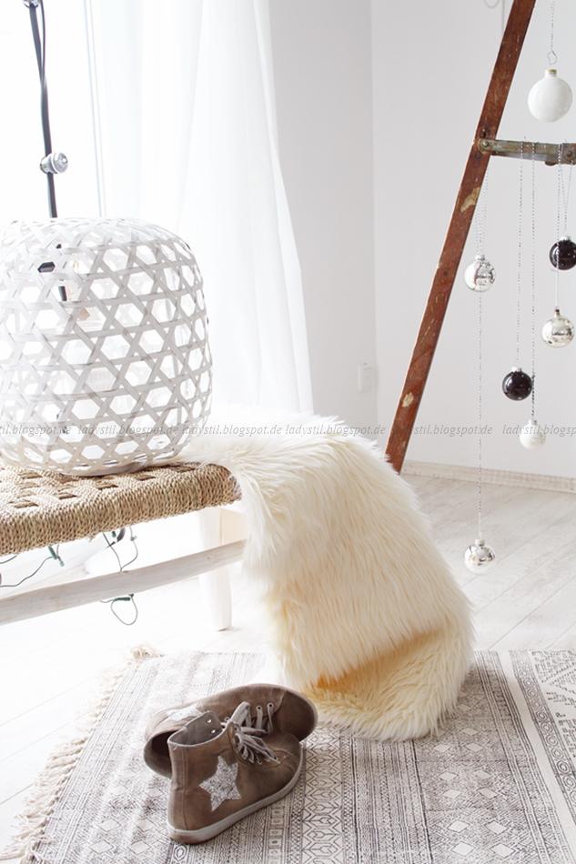 Blick auf einen Teppich mit Schuhen und einer Sitzbank mit Fell vor der Leiter mit Weihnachtskugeln geschmückt