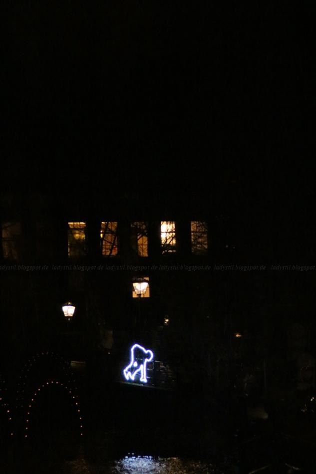 Lichtkunst an der Gracht über einer Brücke springende Menschen