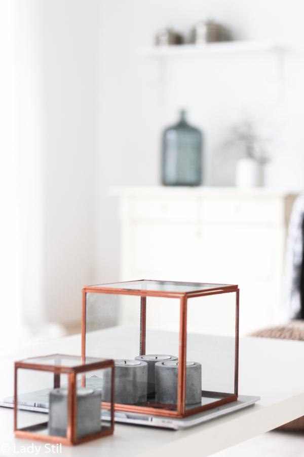 kupferfarbene Glaskästchen als Dekoelement auf einem weißen Tisch