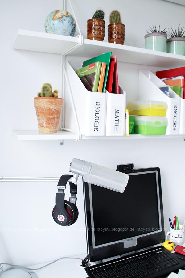 Schreibtischansicht mit Computer Kopfhörern und Regalansicht mit Ordnern nach Schulfach sortiert