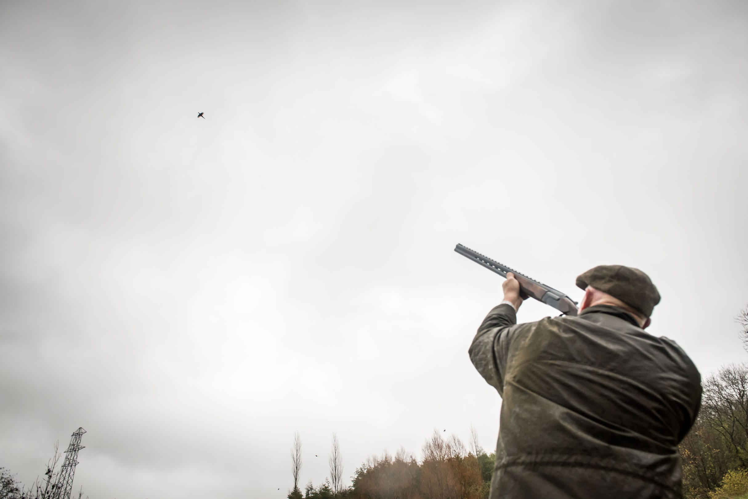 Gentleman aiming at a game bird while shooting at Lady's Wood Shooting School