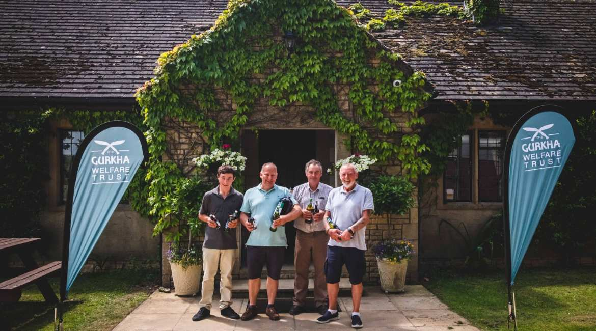The winning team pose in front of the shooting lodge
