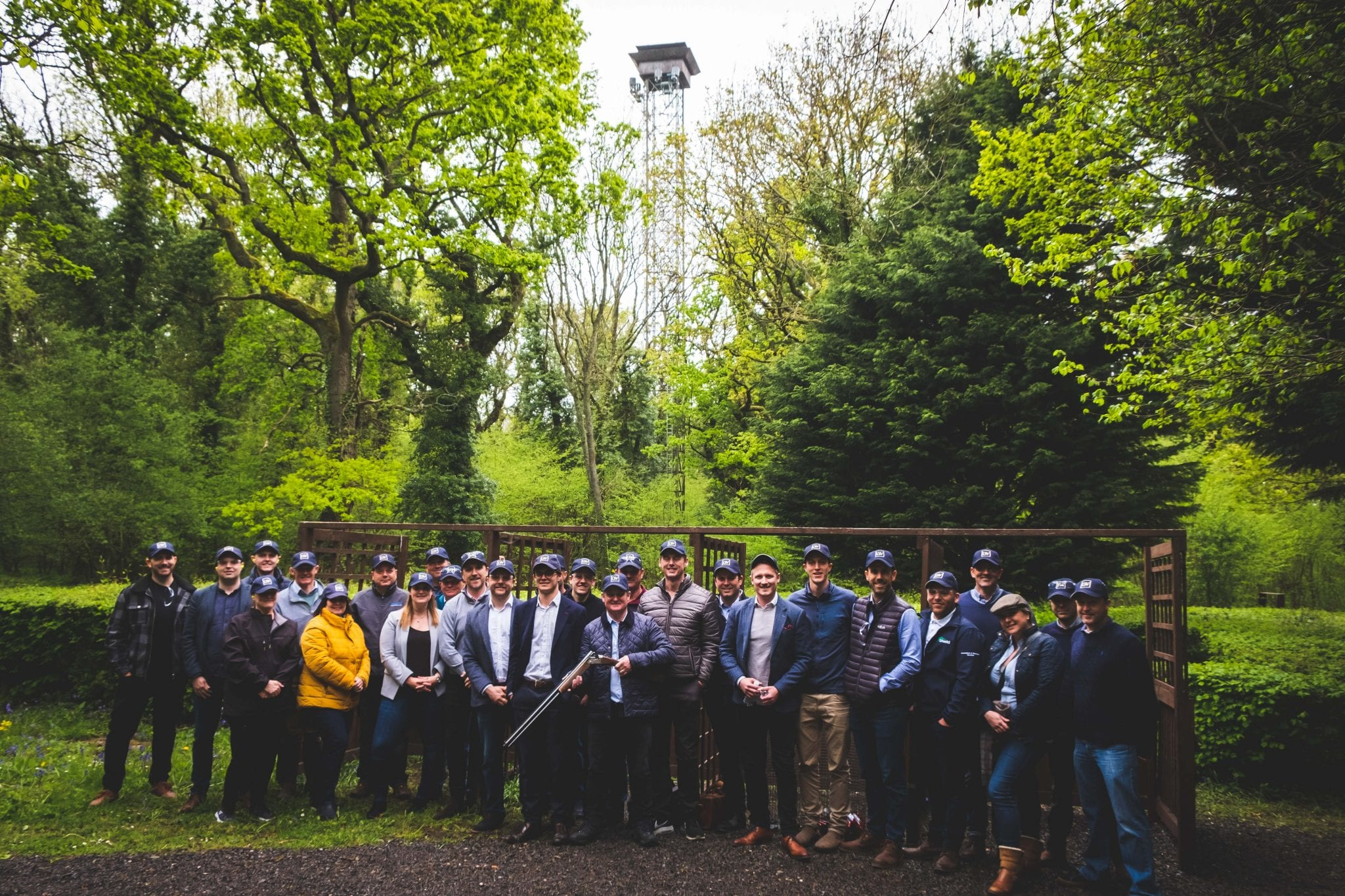 A group pose underneath Lady's Wood high tower at a corporate event in Bristol