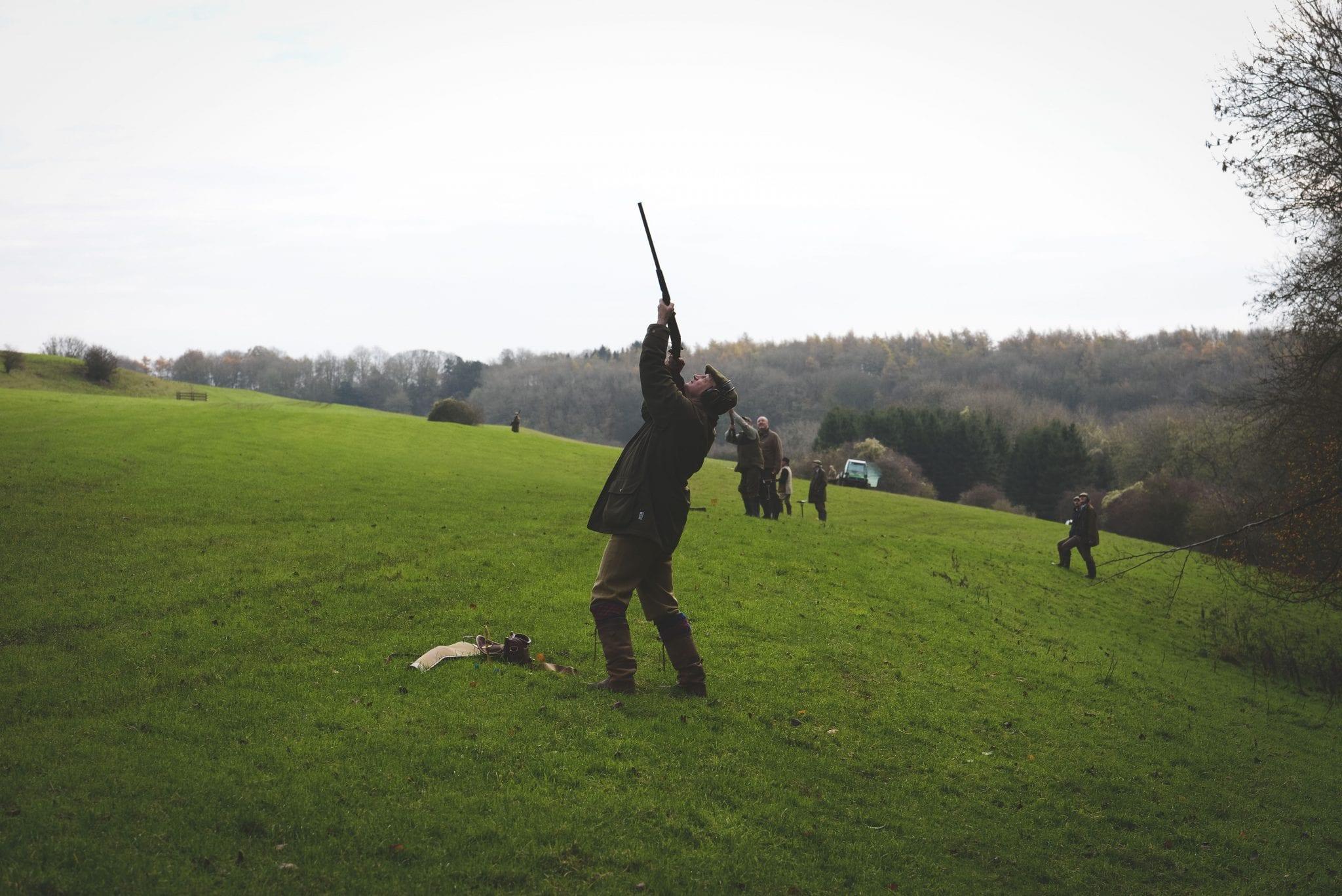 A gun aims at bird during a game shooting drive